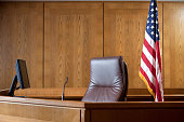 An empty courtroom bench with U S flag