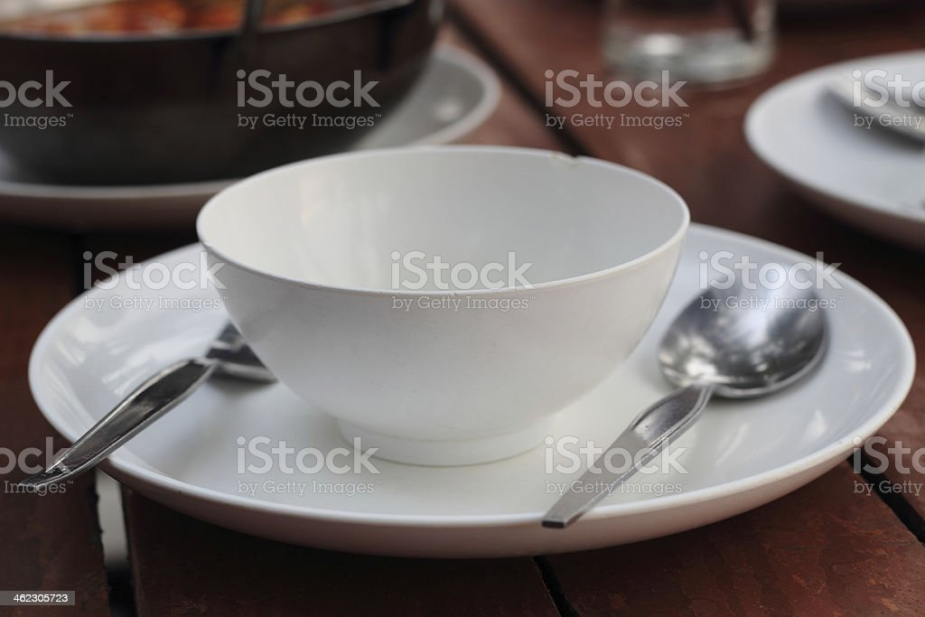 An empty cup with plate, fork and spoon on table royalty-free stock photo