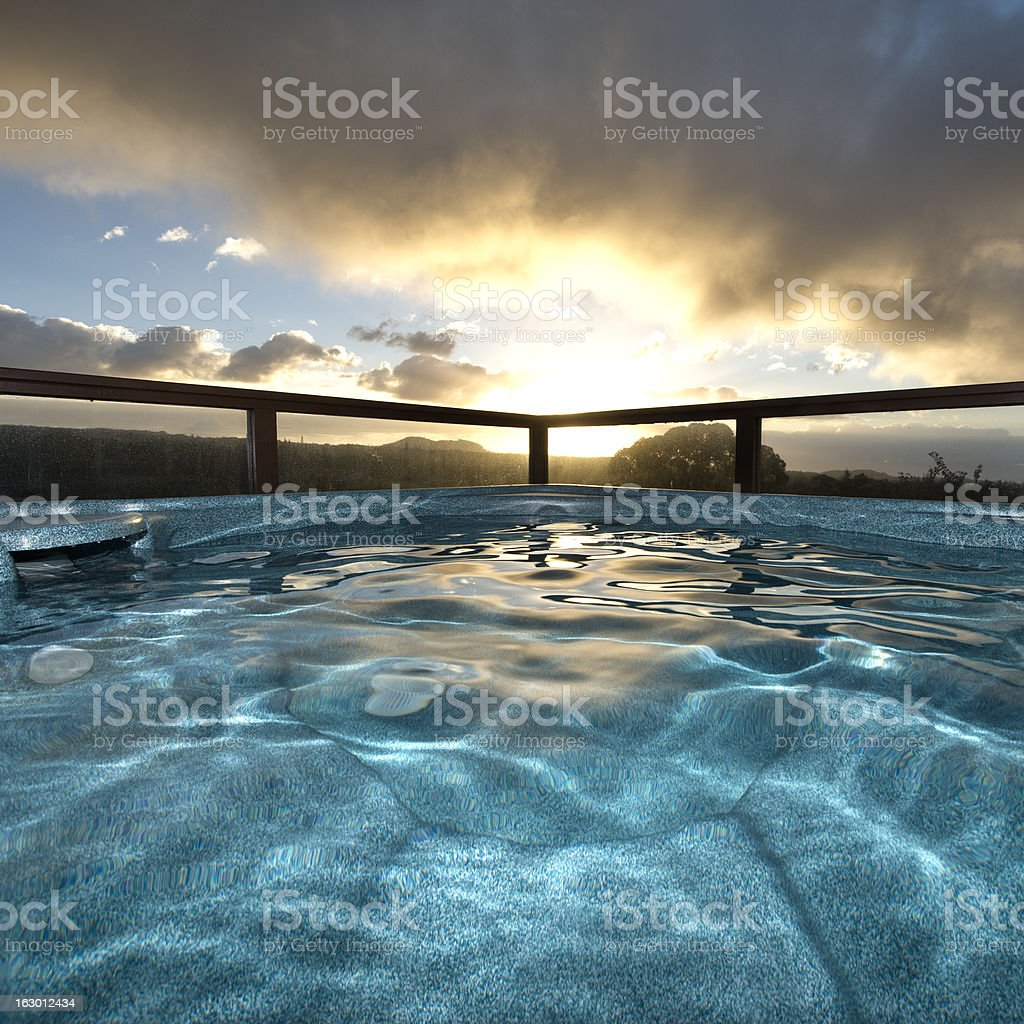 An empty, outdoor, blue hot tub at sunrise stock photo