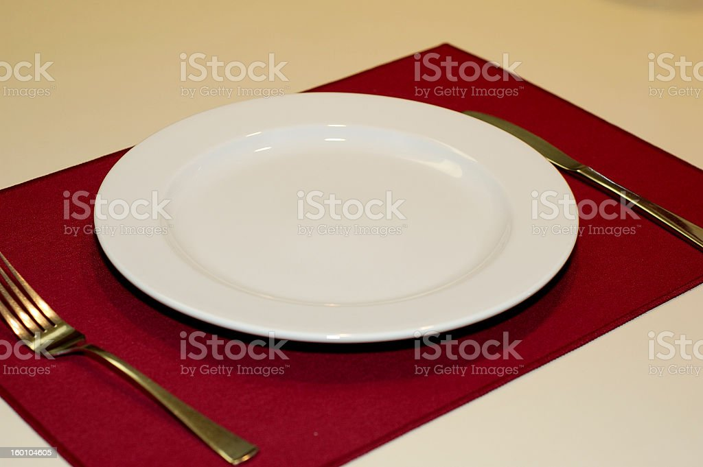 An empty plate with fork and a knife on a red mat royalty-free stock photo