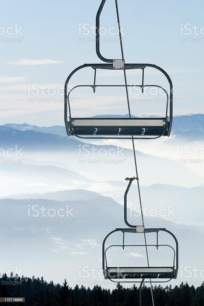 An empty ski lift with the view of the mountains stock photo