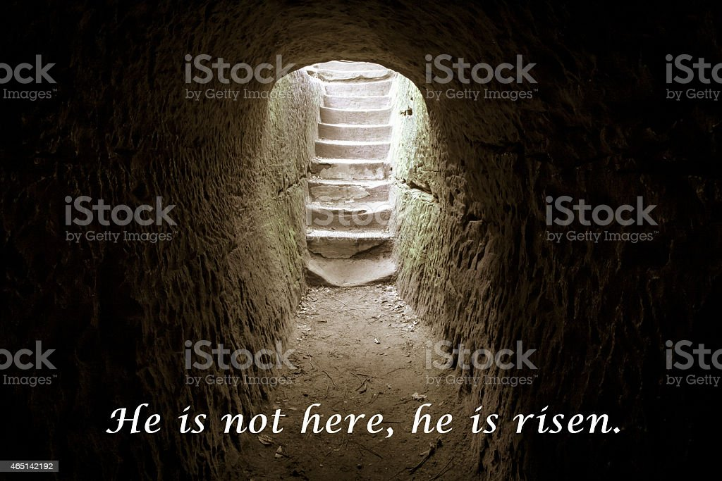 An empty tomb leading to a brightly lit staircase stock photo