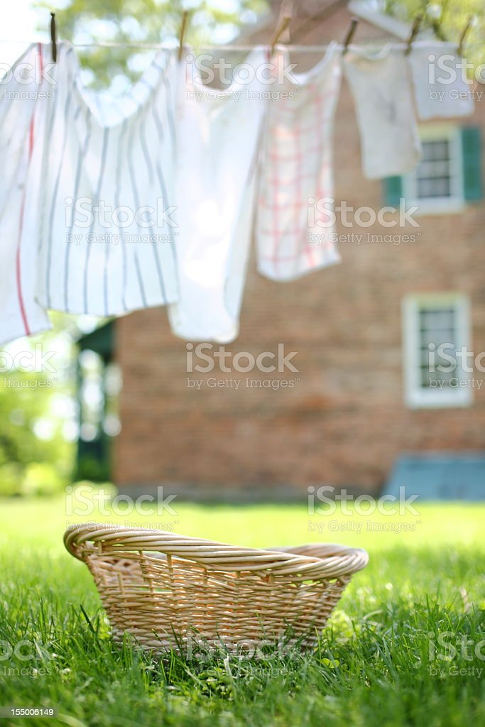An empty wicker basket beneath an outdoor clothesline stock photo