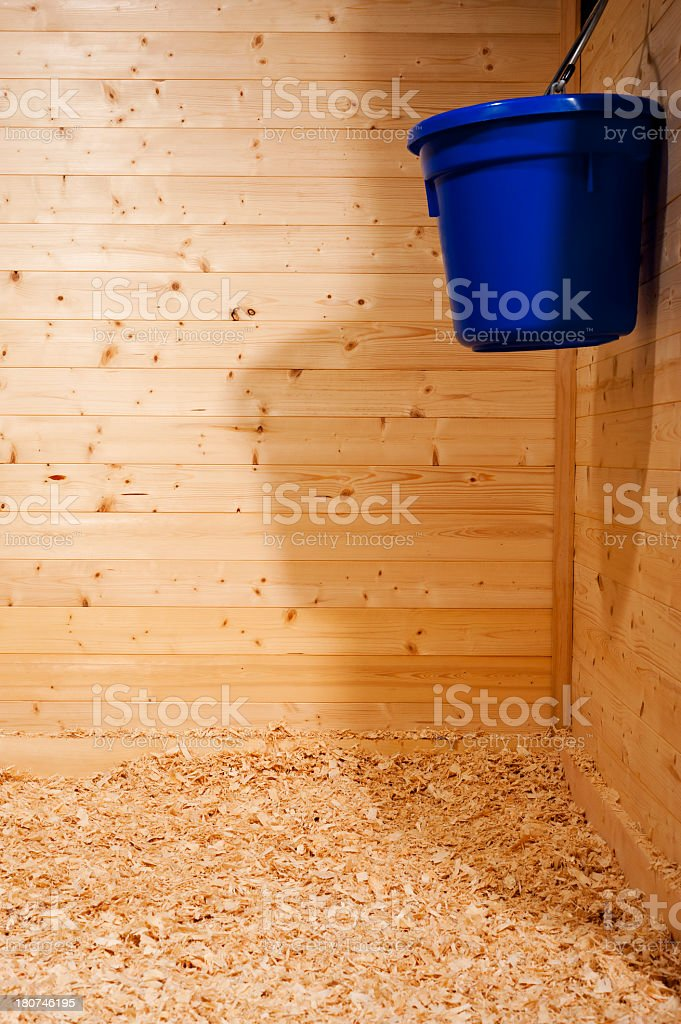 An empty wooden planked stall with animal bedding in a barn royalty-free stock photo