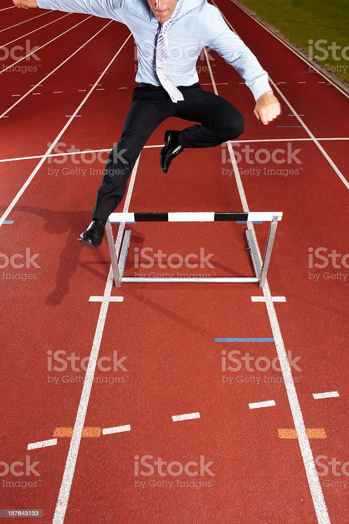 An energetic businessman is jumping over the hurdle royalty-free stock photo