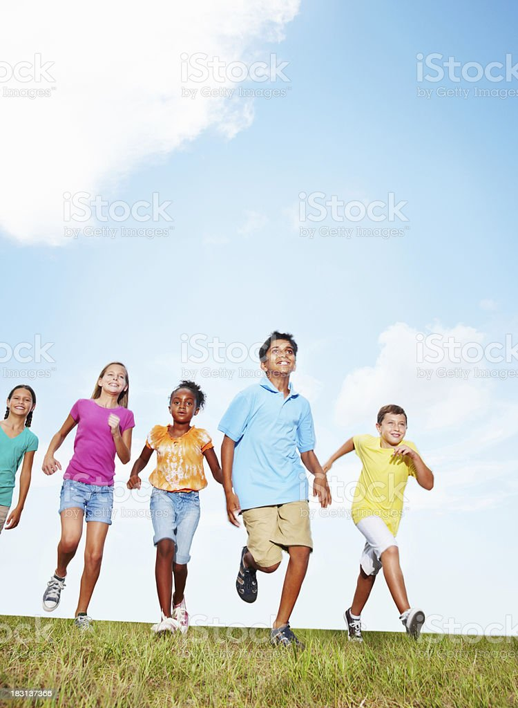 An energetic friends running on grass against sky - copyspace royalty-free stock photo