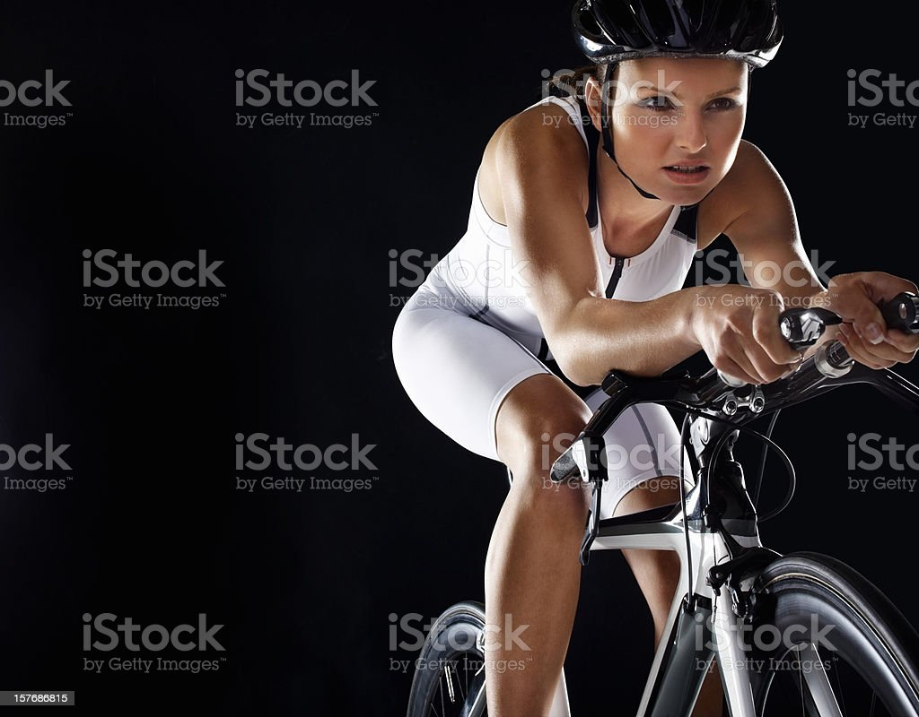 An energetic woman riding bicycle against black background royalty-free stock photo