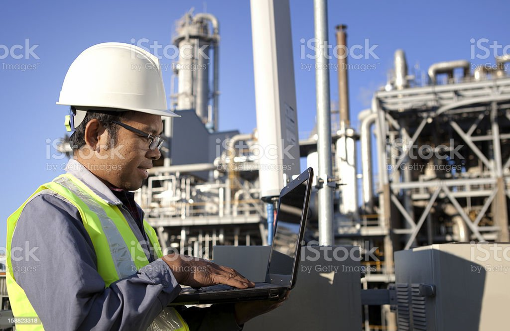 An engineer at a power plant working on a laptop royalty-free stock photo