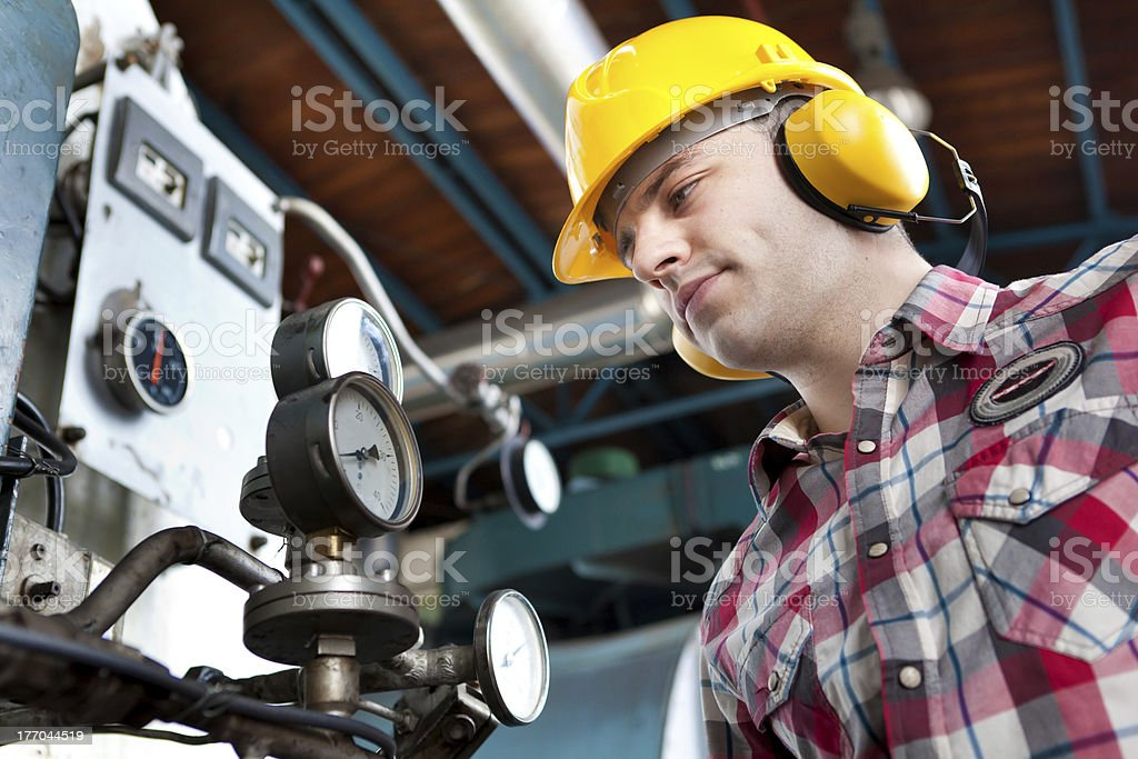 An engineer at work wearing a hard hat and ear defenders stock photo