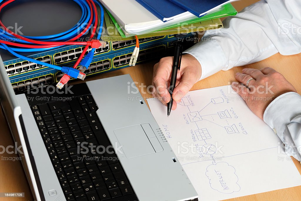 An engineer drawing on paper in front of a laptop stock photo