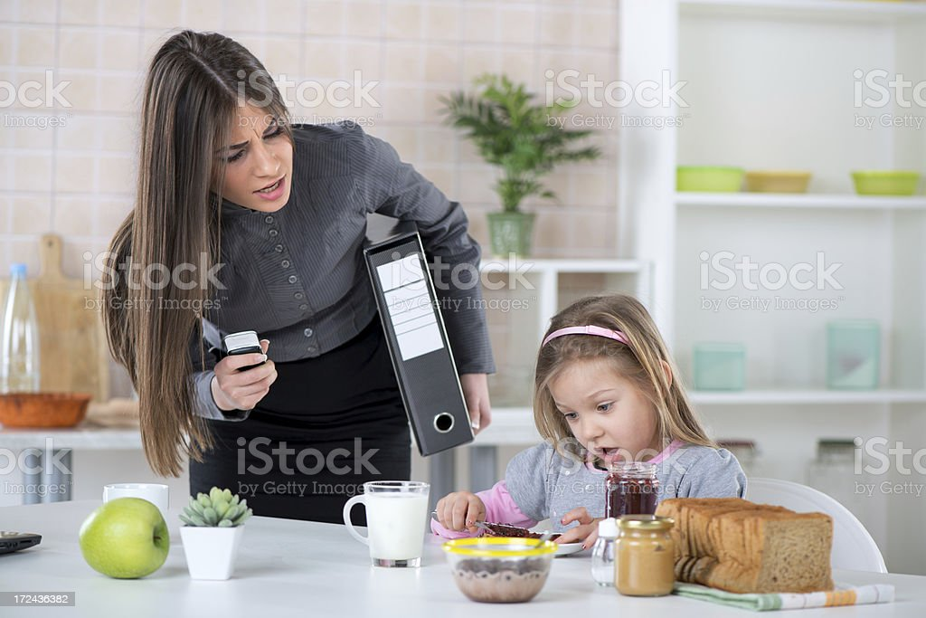 An exasperated mother running late and yelling at her child stock photo