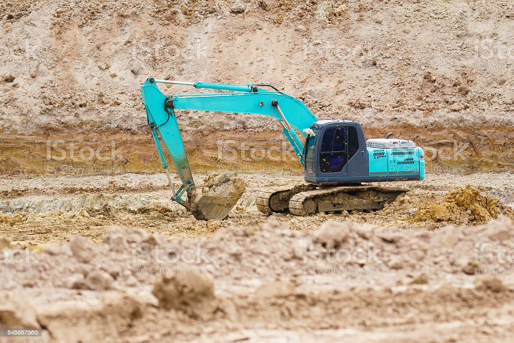 An excavator working removing earth on a construction site. stock photo