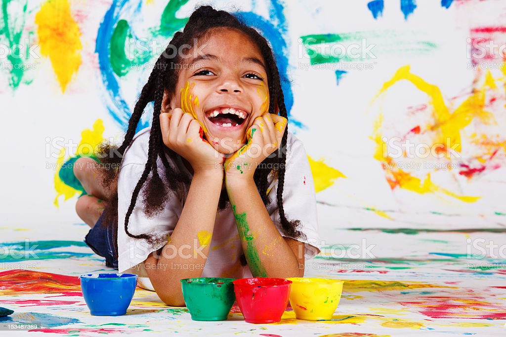 An excited girl playing with paint stock photo