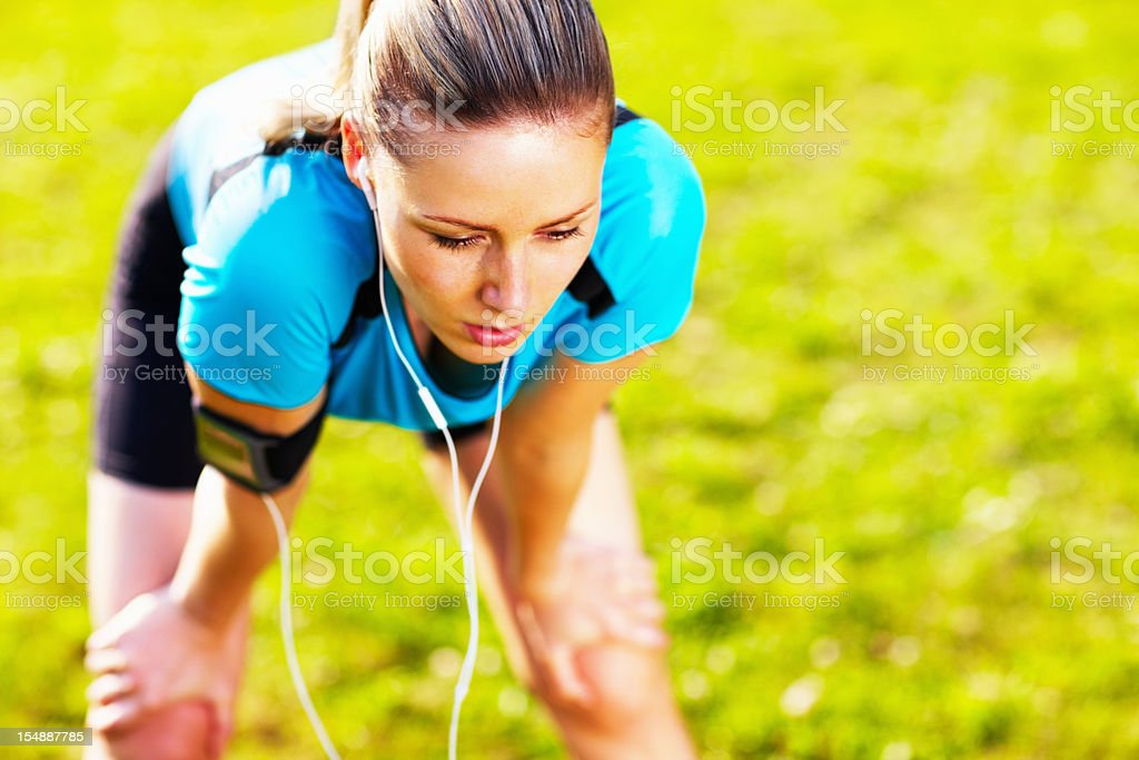 An exhausted woman after jogging in a park royalty-free stock photo