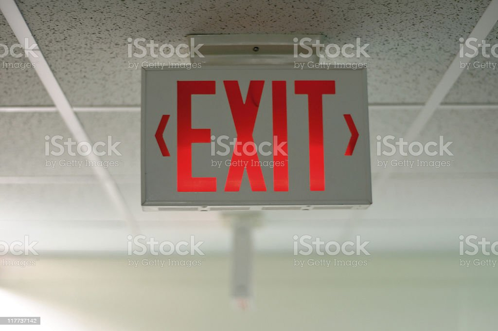 An exit sign hanging from a ceiling stock photo