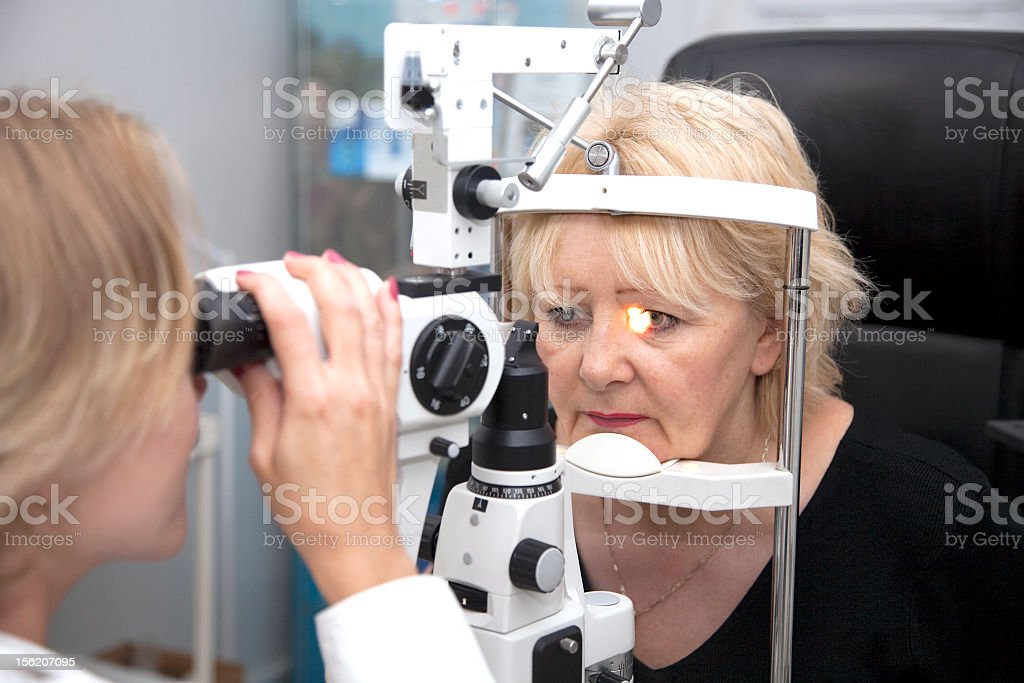 An eye doctor is examining a patients eyes at an office royalty-free stock photo