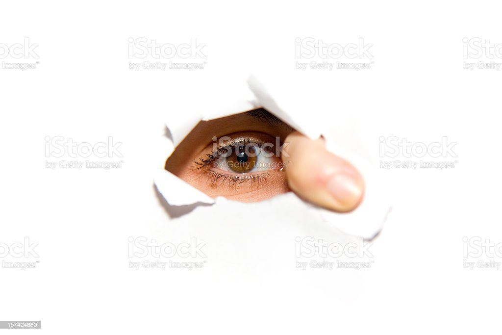 An eye looking through a hole in the wall royalty-free stock photo