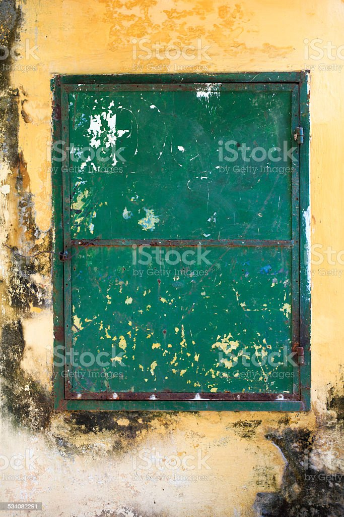An green old steel door with yellow wall. royalty-free stock photo