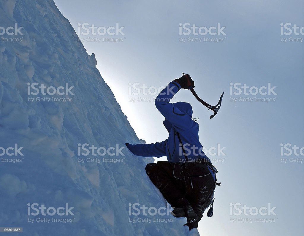 An ice climber ascending a mountain of ice with axe stock photo
