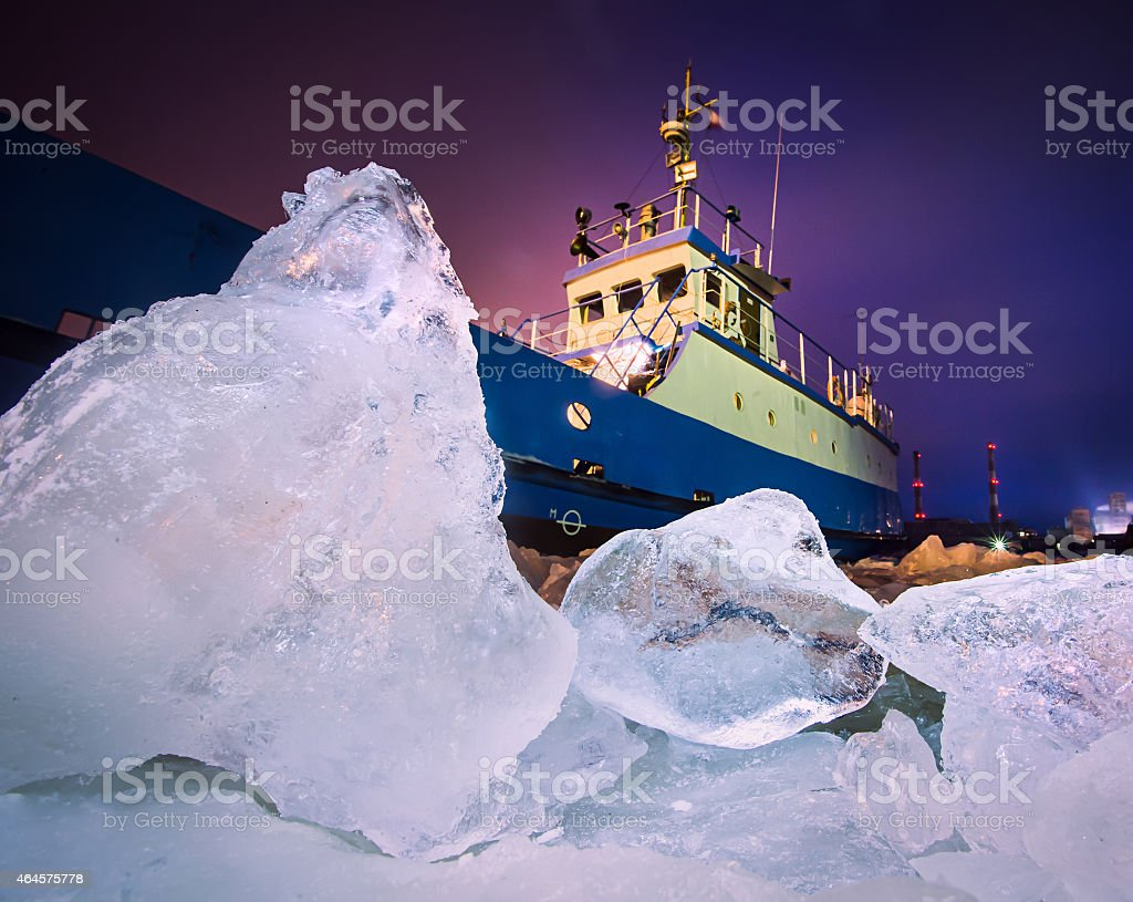 An iceberg with a ship trying to go through stock photo