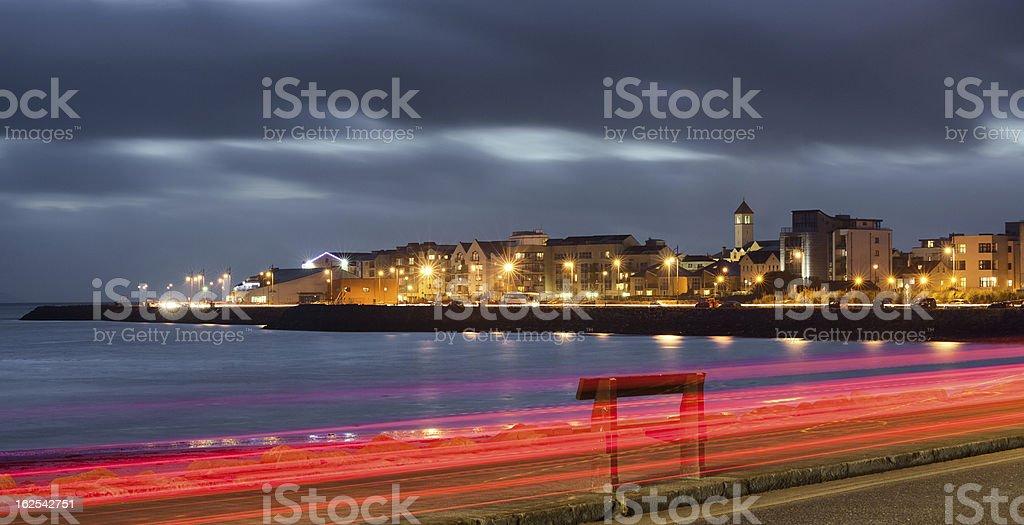 An illuminated city at night at the bank of an ocean bay stock photo