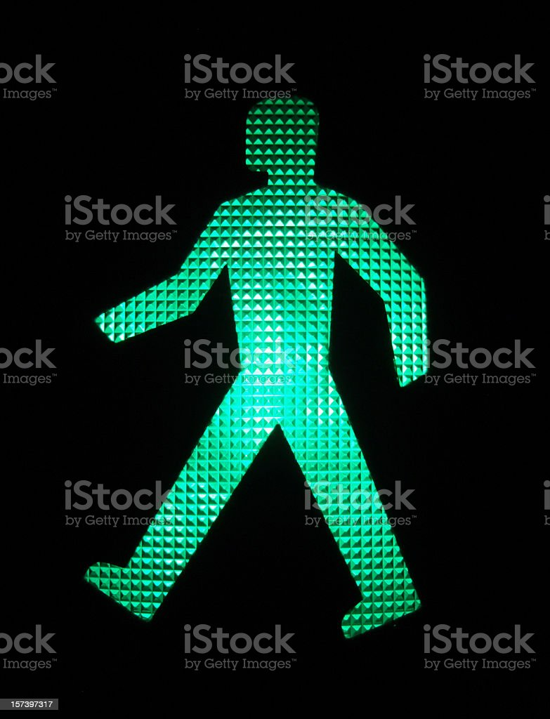 An illuminated green LED image of a walking person stock photo