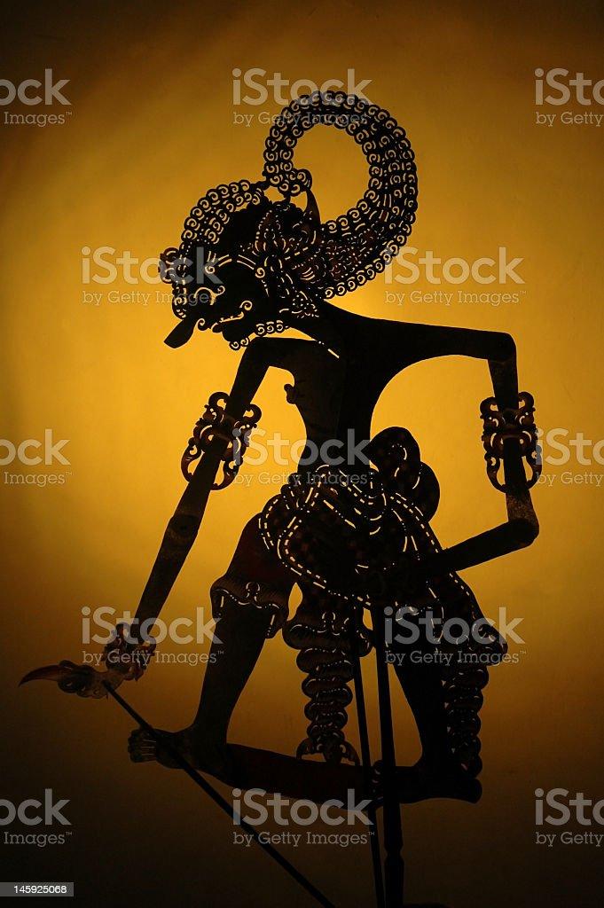 An illustrated black wayang Java against orange background stock photo