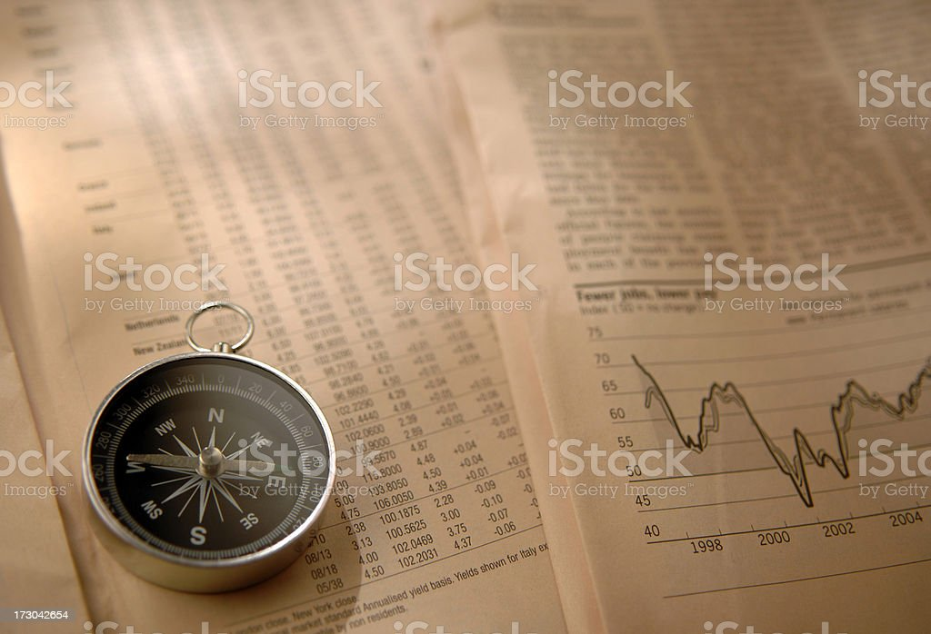 An image of a compass on financial pages royalty-free stock photo