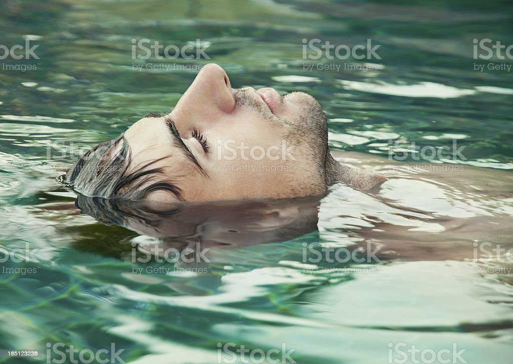 An image of a man with his eyes closed floating in water stock photo