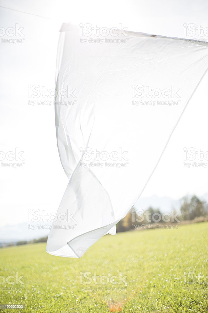 An image of a sheet drying on a clothesline stock photo