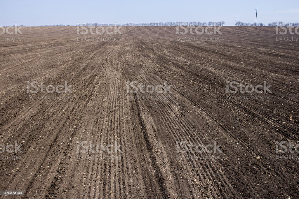 an image of black ploughed field under blue sky stock photo