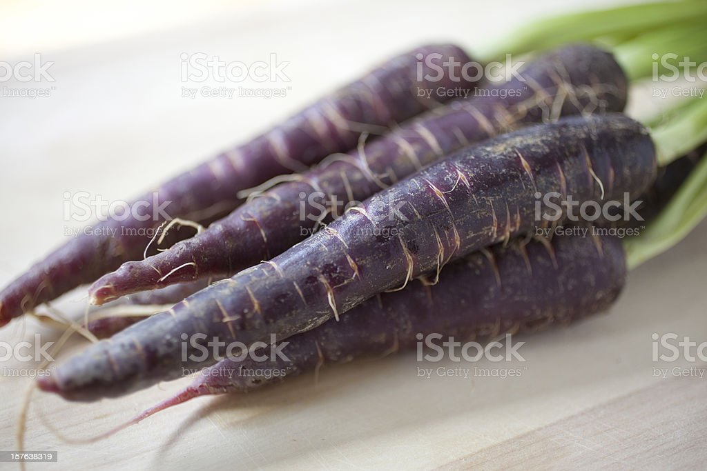 An image of four purple nutritious carrots royalty-free stock photo