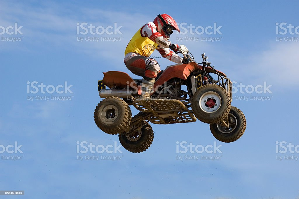 An impressive quadbike jump on mid-air caught from below stock photo