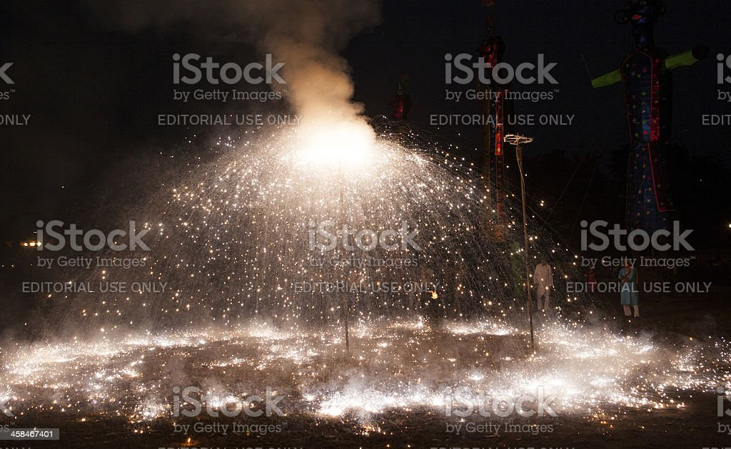 An Indian Hindu devotee looks on as fire crackers burn stock photo