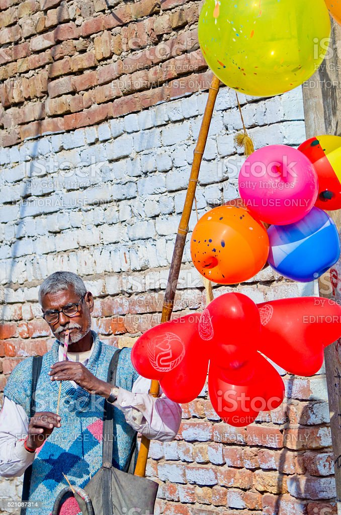 An Indian man playing music and selling balloons stock photo