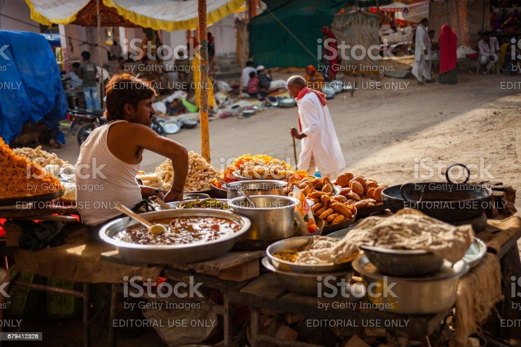 An Indian Rajasthani man at his sweets stall at Chaksu fair in Jaipur stock photo