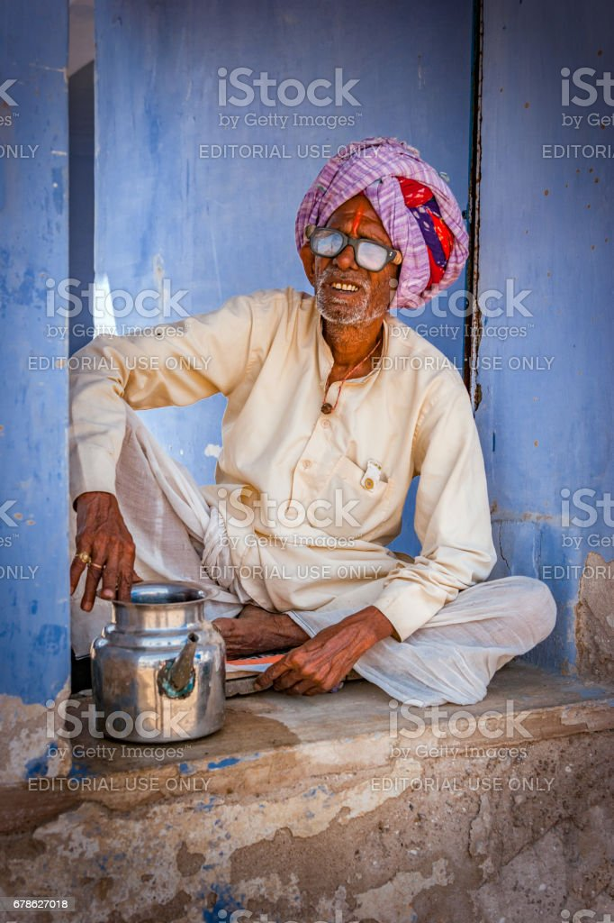 An Indian rajasthani old man serves at Pyaaoo - a place to give water to thirsty visitors at free of cost, Chaksu in Jaipur stock photo