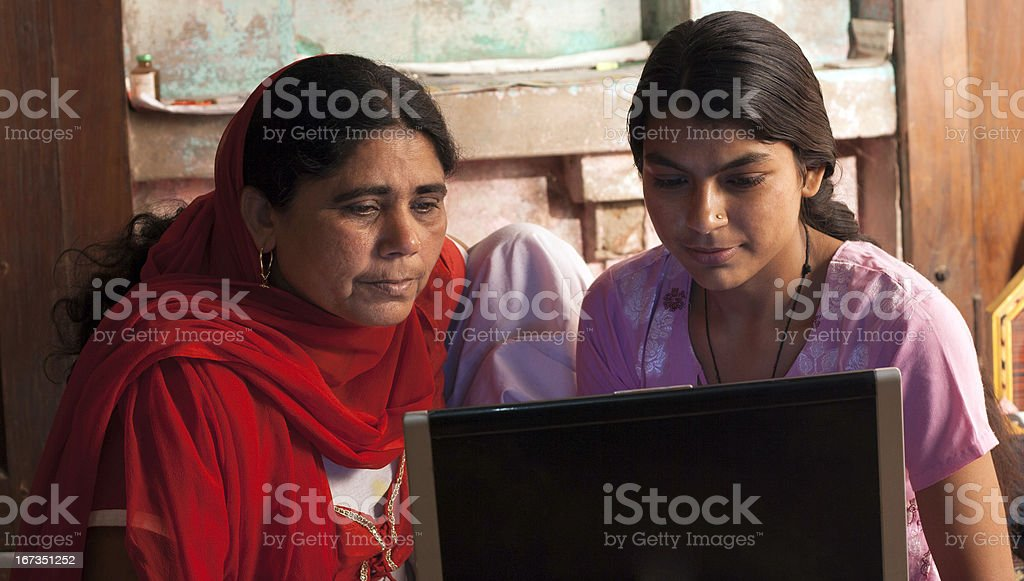 An Indian woman with her mother viewing the laptop computer stock photo
