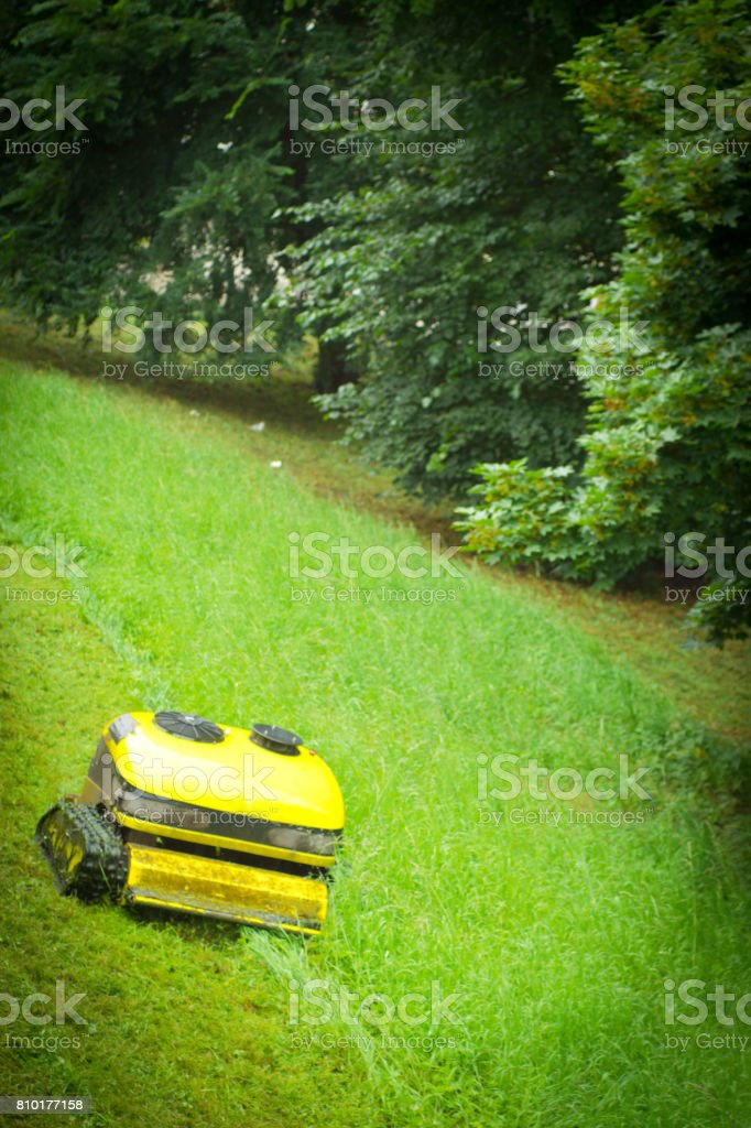 An industrial grade rechargeable remote control lawnmower stock photo