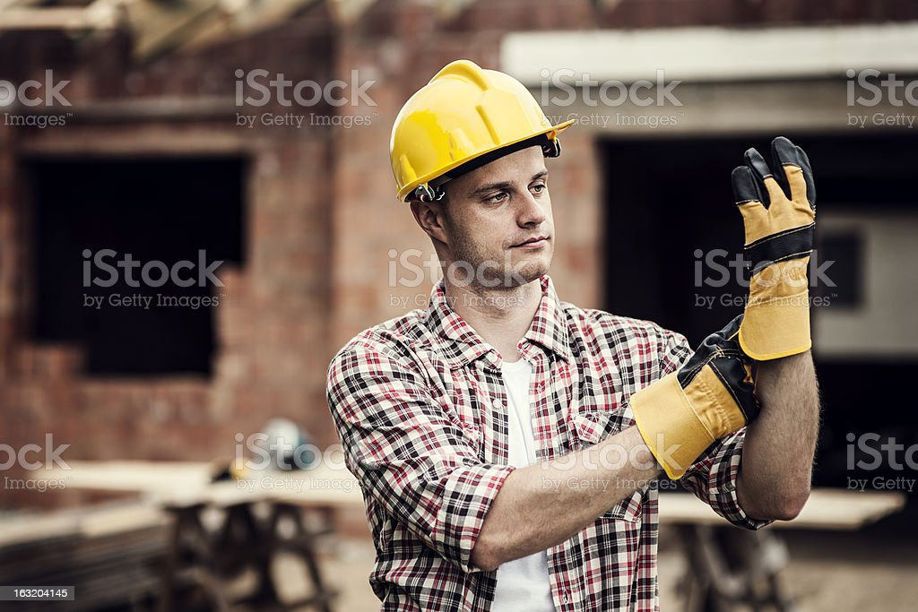 An inebriated construction working staring at his hand royalty-free stock photo