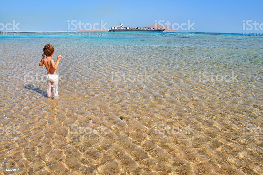 An infant boy standing in the deserted sea, in pants stock photo