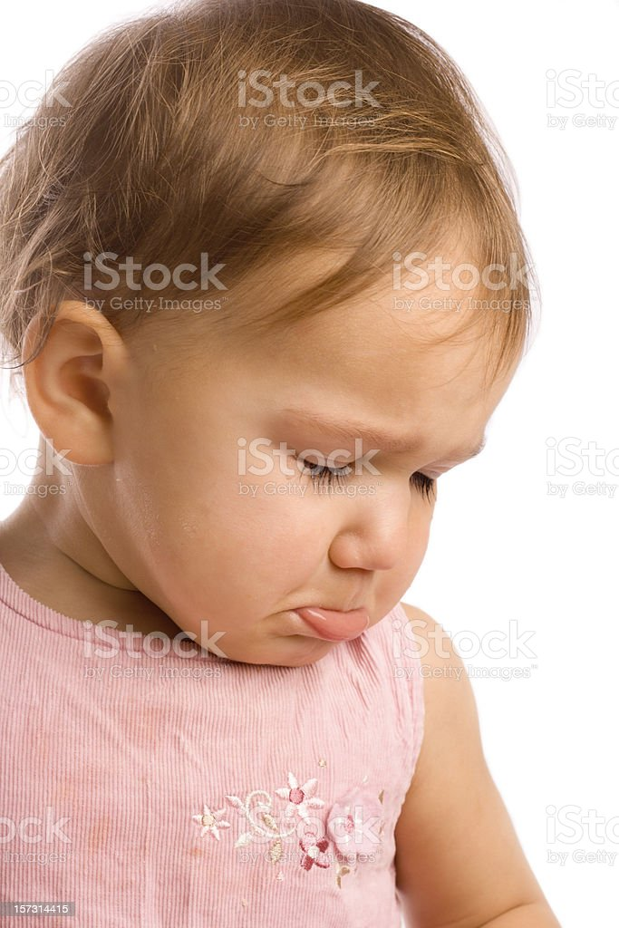 An infant girl pouting in a pink outfit stock photo