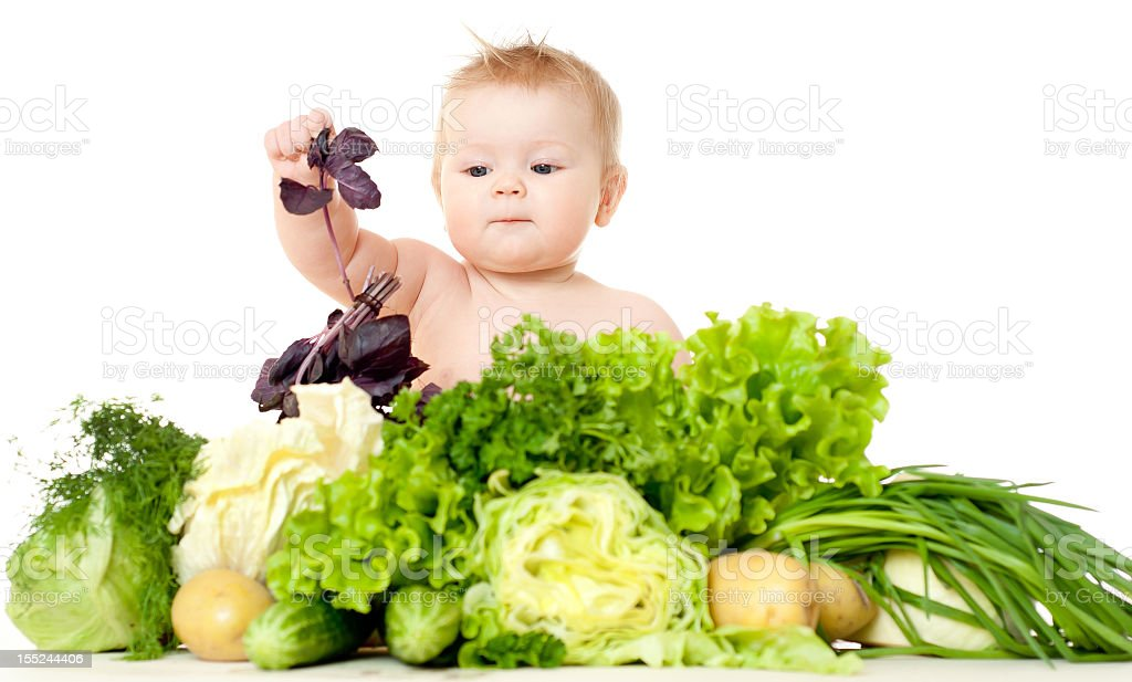 An infant playing with different types of vegetables royalty-free stock photo