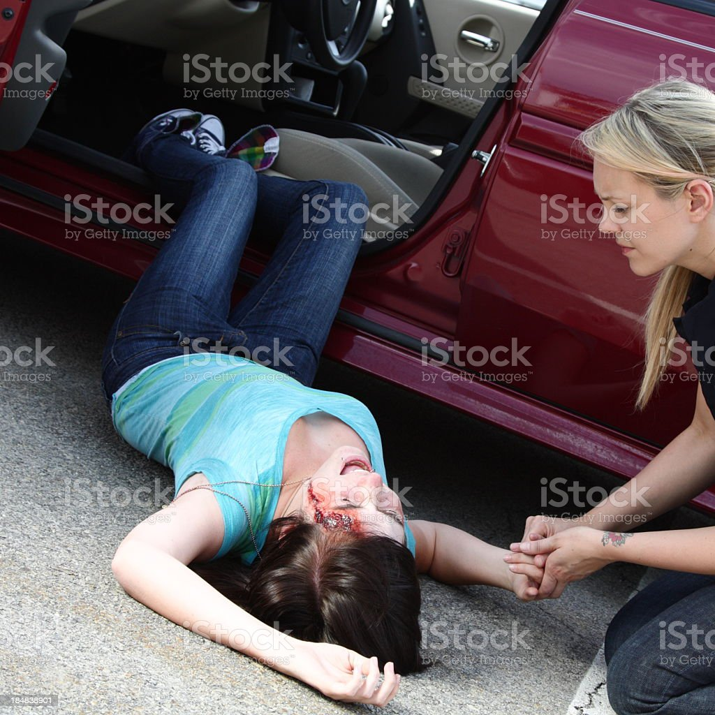 An injured driver, lying on the road after a car accident stock photo