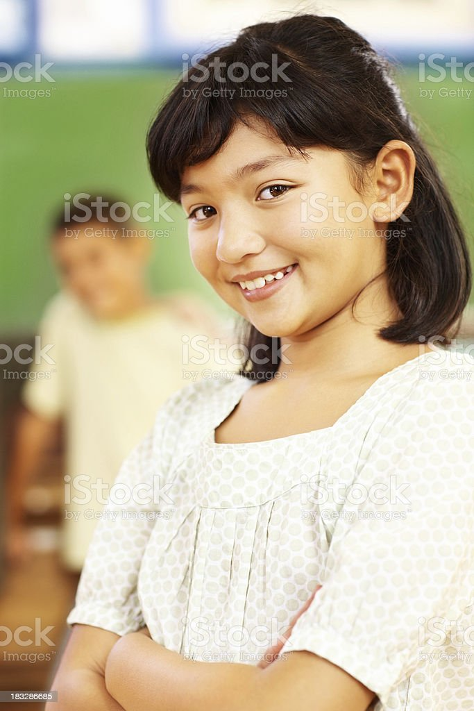 An innocent schoolgirl smiling confidently with her classmates royalty-free stock photo