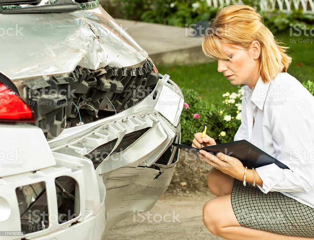 An insurance adjuster looking at the damaged bumper of a car stock photo