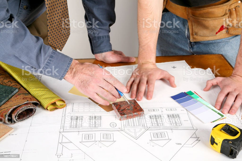 An interior design plan with two people looking over it royalty-free stock photo
