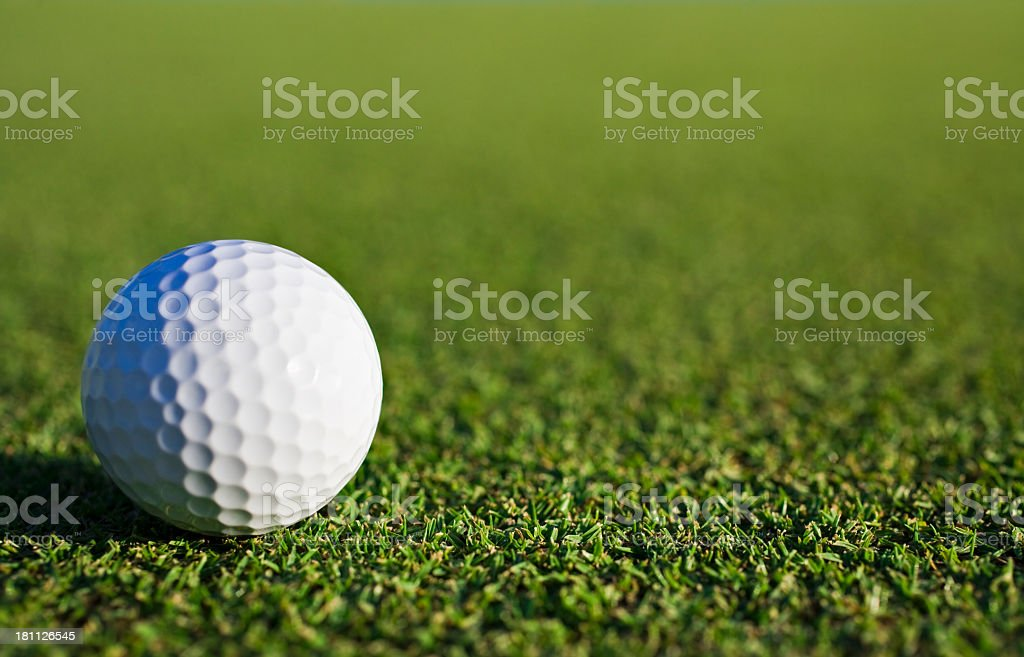 An isolated golf ball on the green stock photo