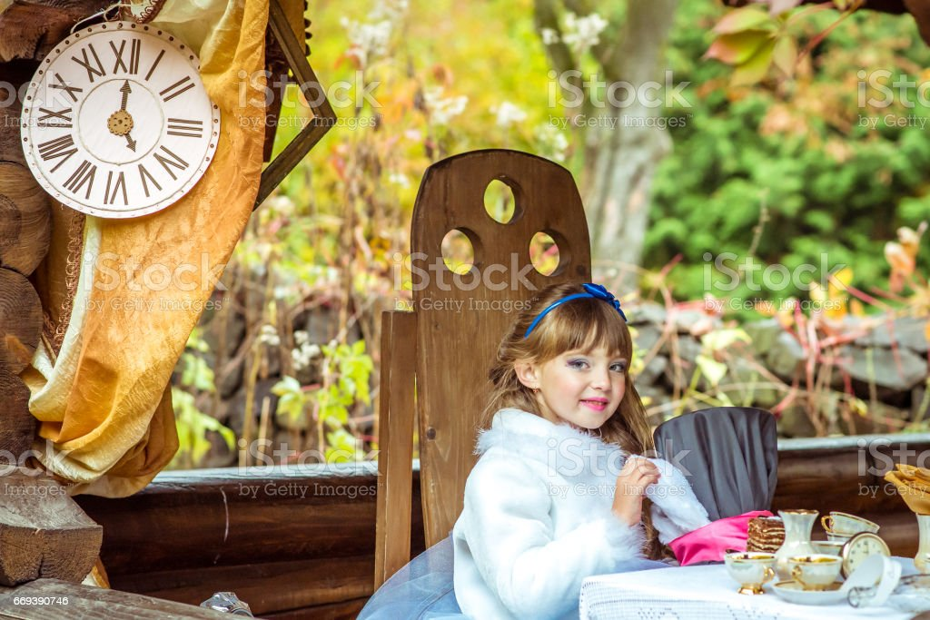 An little beautiful girl holding cylinder hat with ears like a rabbit in the hands at the table stock photo