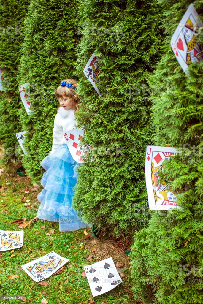 An little beautiful girl standing near the fir trees and looking down at the playing cards stock photo